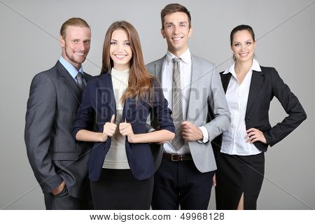 Business team standing in row on grey background
