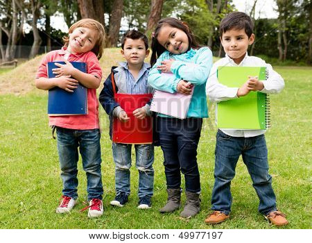 Happy group of school kids holding notebooks outdoors