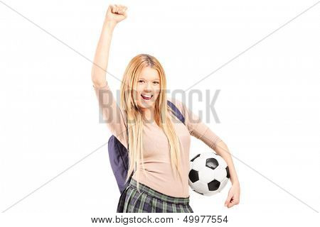 Euphoric female student with backpack holding a soccer ball isolated on white background