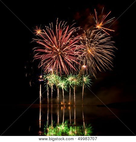 Bursts Of Red, Orange And Green Fireworks
