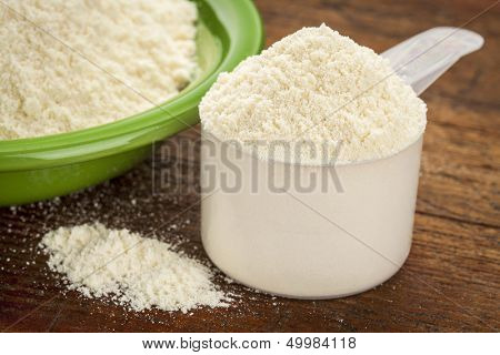 measuring scoop of whey protein powder with a bowl on wooden surface