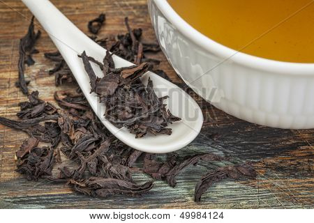 a cup of oolong black tea with loose leaf and teaspoon