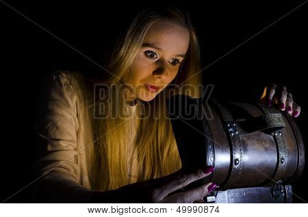 woman opening a small chest in the dark