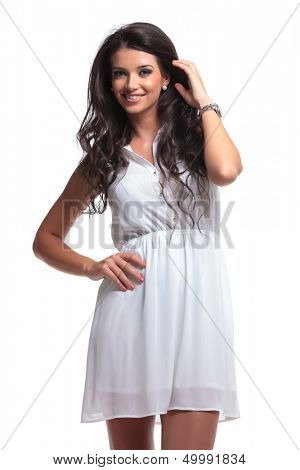 young beautiful woman holding a hand on her hip and the other in her hair while smiling for the camera. isolated on a white background