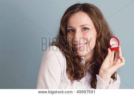 Portrait Of Smiling Surprized Woman With Ring In Hand