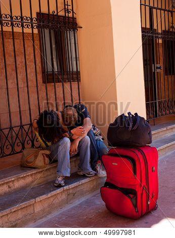 Young People Sleeping On The Sidewalk