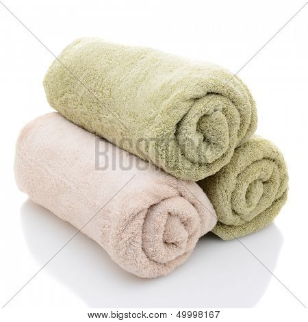 Three rolled bath towels freshly laundered on a white background with reflection. Closeup looking at the towel ends.