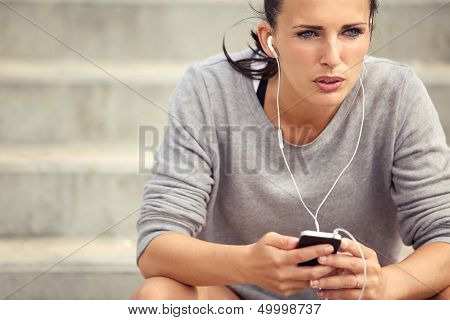 Serious Female Runner Listening To Music