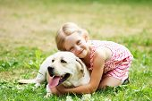 A little blond girl with her pet dog outdooors in park