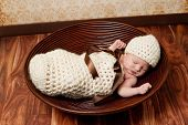 stock photo of beanie hat  - 8 day old newborn baby girl sleeping in a crocheted cream colored cocoon - JPG