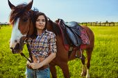image of cowgirl  - brunette cowgirl woman posing with horse outdoors portrait - JPG