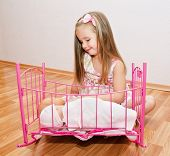 stock photo of baby doll  - Cute smiling little girl playing with her newborn baby dolls in room - JPG