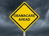 pic of mandates  - An warning sign against a stormy sky with words Obamacare Ahead Warning about Obamacare - JPG