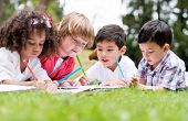 stock photo of bonding  - Group of school kids coloring outdoors looking happy - JPG
