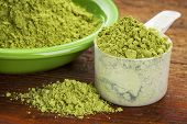 stock photo of oleifera  - measuring scoop of moringa leaf powder with a bowl on wooden surface - JPG