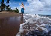 foto of wet feet  - Young lady walking on a wet sandy beach - JPG