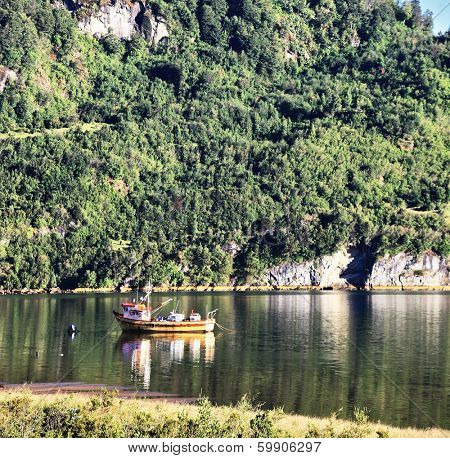 Charming quiet backwater in the river next to the road. Red fishing boat reflected in the smooth surface of the water.  Carretera Austral - the famous road in the Chilean Patagonia