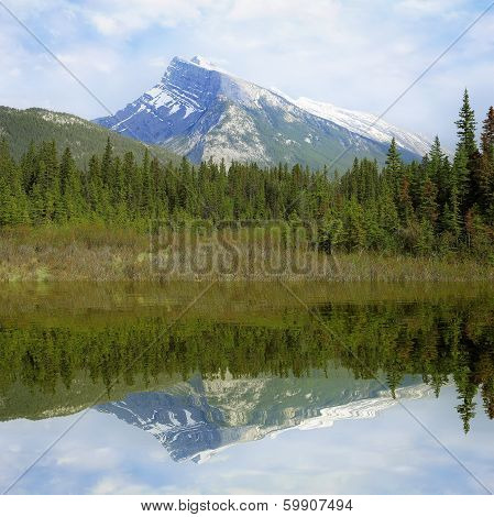 Rundle mountain and its reflection.