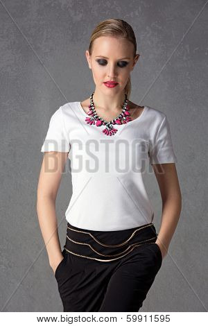 upper body portrait of a young blond woman wearing white t-shirt, statement pink necklace and black pants