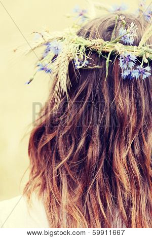 Beautiful young girl in summer field with grain and flower garland