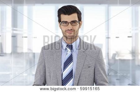 Portrait of young corporate businessman at office, smiling.