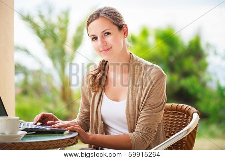 Portrait of a pretty young woman working on her computer on a terrace of her house