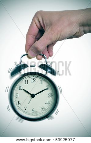 someone holding a typical mechanical alarm clock ringing