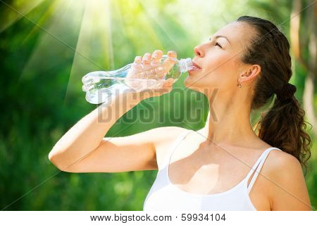 Young Woman Drinking Water from the bottle. Healthy and Sporty Girl Doing Sport Outdoor. Workout