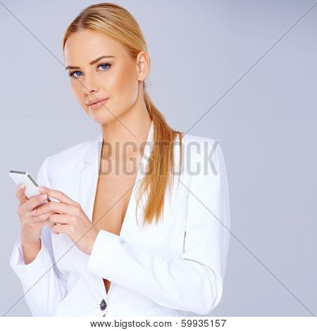 Beautiful stylish blond woman in a glamorous white jacket with a plunging neckline using a mobile phone and looking at the camera  on grey