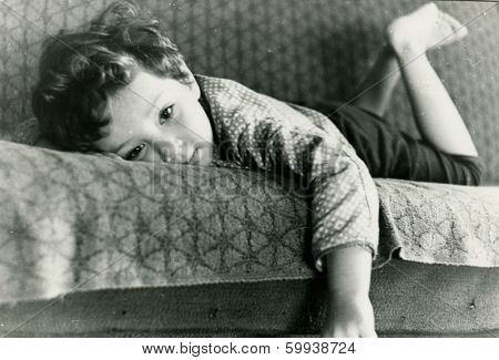KURSK, USSR - CIRCA 1976:  An antique photo shows  portrait of a little boy lying on the sofa.