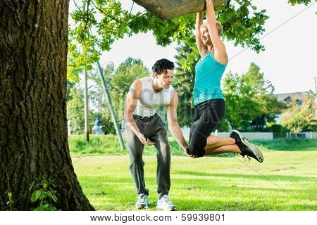 Young woman and personal trainer exercising chins or pull ups in City Park under summer trees for sport fitness