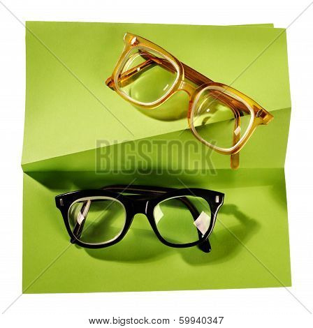 Two pairs of retro eyeglasses on creative support.