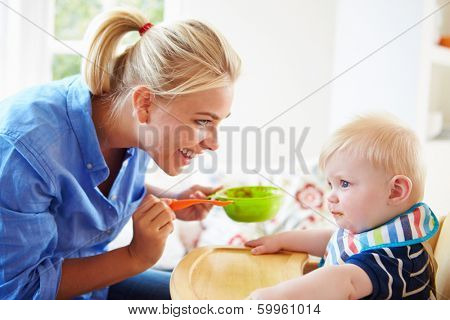 Mother Feeding Baby Boy In High Chair