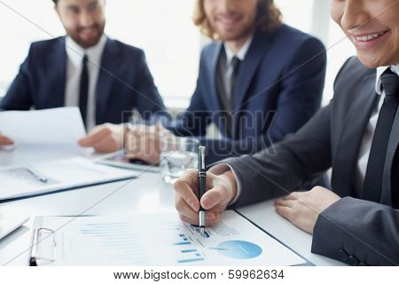 Three men discussing spreadsheet with charts