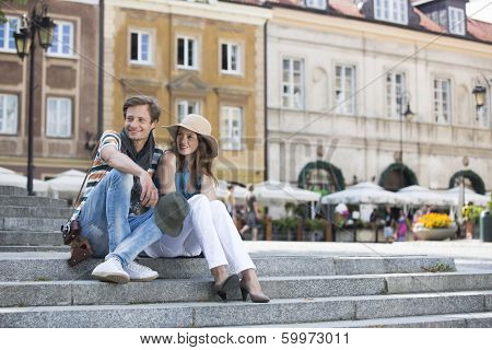 Tourist couple sitting on steps against building