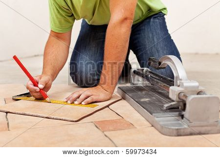 Worker Hands Laying Ceramic Floor Tiles