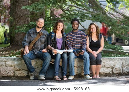 Full length portrait of confident university students sitting on parapet at campus