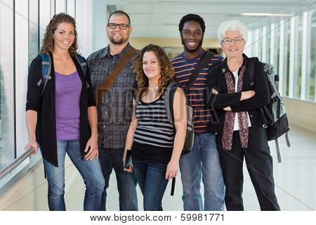 Group portrait of confident multiethnic university students standing in corridor with professor