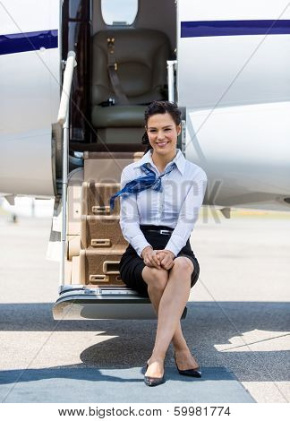 Full length portrait of beautiful air hostess sitting on ladder of private jet