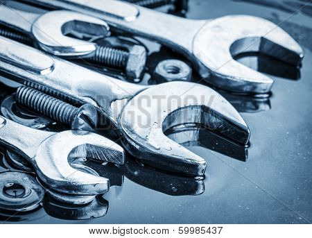Set of tools wrenches and bolts toned in metallic blue with reflections