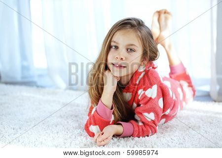 Portrait of child in soft warm pajamas lying down on the carpet at home
