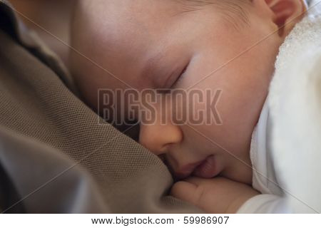 Moments of tranquility and warmth: Close up of adorable baby boy sleeping peacefully on he's mother chest.