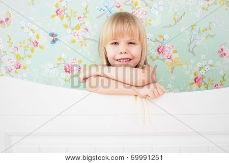 Little adorable girl with a sly smile standing behind a bed