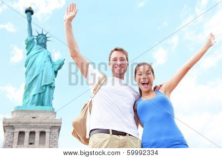 Travel tourists couple at Statue of Liberty, New York City, USA. Multiracial tourist couple on summer vacation holidays cheering celebrating happy. Asian woman, Caucasian man.