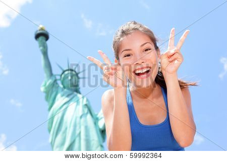 Tourist at Statue of Liberty, New York, USA making funny face expression victory hand signs excited and happy. Tourism and travel concept with joyful mixed race Asian Caucasian woman.