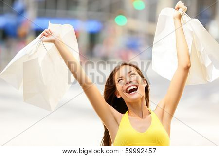 Happy shopping woman in excited winning and cheering holding shopping bags up in air. Shopper on shopping spree. Young multiracial Asian Caucasian girl in dress in New York City, Manhattan, USA.