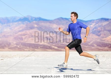 Man running outdoor sprinting for success. Male fitness runner sport athlete in sprint at great speed in beautiful landscape in desert.