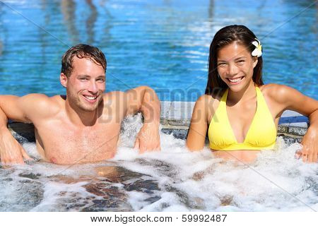 Hot tub - Couple in spa wellness jacuzzi. Portrait of beautiful young couple looking at camera on luxury resort spa retreat. Handsome man and beautiful asian woman.