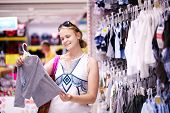stock photo of blouse  - Attractive young mother shopping for childrens clothes in a retail clothing store viewing items on a rack - JPG