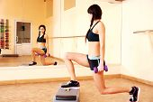 Young happy fit woman doing exercises with dumbells on step board and looking on her reflection in m
